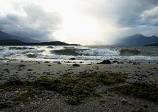 Breaking waves on Lake Manapouri. Early morning light and waves breaking over the sands on the shores of Lake Manapouri Royalty Free Stock Photo