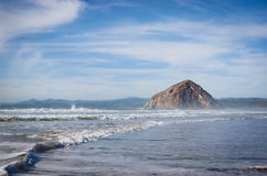 Breaking waves and Morro Rock. Pacific Ocean surf on the Montana de Oro State Park sand spit just south of gigantic Morro Rock. The rock is in Morro Bay, the Stock Photography