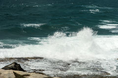 Breaking waves over rocks Stock Image
