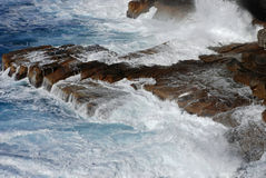 Breaking of Waves. Waves breaking over the shoreline rocks at Watson's Bay Cliff in Sydney NSW Australia Royalty Free Stock Image