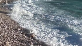 Breaking waves and roaring. Breaking waves beating and rolling stones and pebbles at the beach stock video