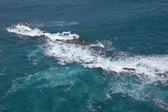 Breaking waves at rocky coast Stock Image
