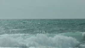 Breaking Waves on the Sea. An unspoilt view of breaking waves on the sea. Clear day, pale greys, gentle splashes. Straight horizon. Shot from shore. Calm stock video footage