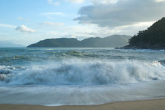 Breaking waves at small beach by the end of the day Stock Photo