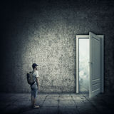 Breakout. Abstract idea with a person standing in a dark room, in front of a opened door. Escape opportunity, entrance to another world royalty free stock photography