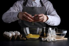 Breaks the egg for dough. recipe pie or cake making concept on dark background.  royalty free stock photography