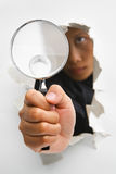 Breakthrough in investigation process. Detective holding magnifying glass from cracked wall means breakthrough in investigation - one of the breakthrough series royalty free stock photos