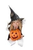 Breakthrough little witch holding a pumpkin Stock Photos