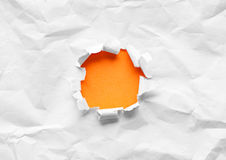 Breakthrough orange paper hole Royalty Free Stock Photography