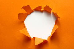 Breakthrough orange paper hole Stock Images