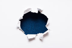 Breakthrough paper hole. With black textured background stock photos