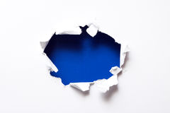 Breakthrough paper hole. With blue textured background royalty free stock photo
