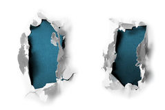 Breakthrough paper holes. With blue textured background Stock Image