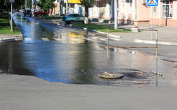 Breakthrough sewerage system. Water flows over the road from the sewer Stock Photo