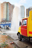 Breakthrough sewerage systems. Fountain and emergency service truck royalty free stock photo