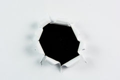 Breakthrough torn big black hole in white paper. Isolated background stock photography
