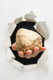 Breakthrough wall holding big gold. Hand breakthrough wall holding lump of golden nugget means breakthrough in finance or similar things - one of the stock image
