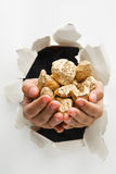 Breakthrough wall holding gold nuggets. Hand breakthrough wall holding lumps of golden nuggets means breakthrough in finance or similar things - one of the stock photography