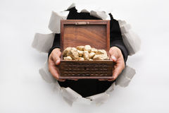 Breakthrough wall holding treasure chest. Hand breakthrough wall holding golden nuggets in treasure chest means breakthrough in finance or similar things - one stock image