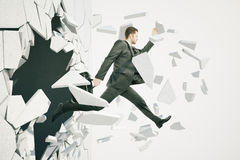 Breakthrough white background. Business breakthrough success concept with businessman jumping through wall on white background royalty free stock photography