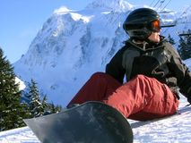 Breaktime. A cute snowboarder takes a break on the hill. Mount Shuksan looms in the background stock image