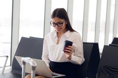 Breaktimezaken Mooie bedrijfsvrouw die aan laptop werken terwijl het wachten op haar vlucht in een luchthaven royalty-vrije stock afbeeldingen