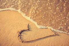 Breakup and divorce. Heart drawn on the beach sand being washed away by a wave. Sand tone. Love affair, summer love or breakup and divorce concept. Ephemeral Stock Photos