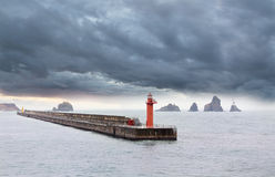 Breakwater with a beacon. The image of a beacon on a concrete breakwater in storm weather Stock Images