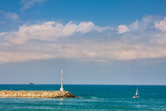 Breakwater with beacon and yacht on Mediterranean  Stock Image