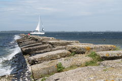Breakwater with a boat Royalty Free Stock Image
