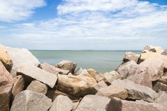 Breakwater at Cassino beach. Rocks of cassino breakwater with beach in background stock images