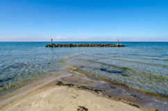 Breakwater in front of beach with shallow water and crossing waves stock photography