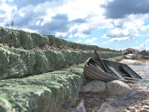 Breakwater with gates and old fishing boat Royalty Free Stock Image