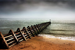 Breakwater Horizon - Norfolk UK. A breakwater structure, intended to lessen tidal erosion, reaches out like a skeletal finger into the North Sea, off the Norfolk Stock Images