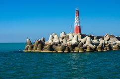 Breakwater and lighthouse on the sea. On sunny summer day Stock Photo