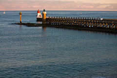 Breakwater with lighthouses in sunrise on atlantic ocean Royalty Free Stock Photography