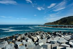 Breakwater made of cubic stones under blue skies with fluffy whi stock photo