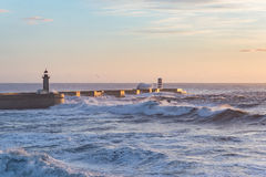 Breakwater pier coast sunset view dusk dawn ocean rough seas waves blue Royalty Free Stock Images