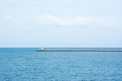 Breakwater pier with small lighthouse. The construction wall in the port to protect the ships from sea waves. Background royalty free stock photography