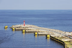Breakwater with the red lighthouse in Kolobrzeg Royalty Free Stock Photos