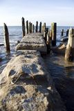 Breakwater in sea. Concrete breakwater with old wooden posts receding into sea Royalty Free Stock Photos