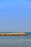 Breakwater in the sea with beacon light on it Royalty Free Stock Photo