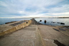 Breakwater in the sea with lighthouse on it Stock Image