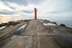 Breakwater in the sea with lighthouse on it Royalty Free Stock Image
