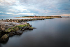 Breakwater in the sea with lighthouse on it Royalty Free Stock Photo