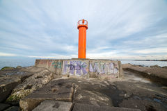 Breakwater in the sea with lighthouse on it Royalty Free Stock Photos