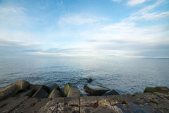 Breakwater in the sea with lighthouse on it Royalty Free Stock Images