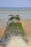 Breakwater in the sea, Middelkerke, West Flanders, Belgium. Couple walking on a breakwater (in the North Sea), Middelkerke, a seaside resort of West Flanders Stock Photos