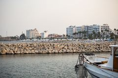 Breakwater of rocks at Cyprus, Larnaca. Summer destination. Beach, sea, town, blue sky background. Royalty Free Stock Photography
