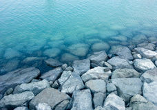 Breakwater stones and rocks near the coastline. Of the blue sea Stock Photography